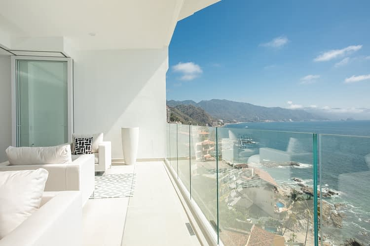Luxury Oceanfront Condo Balcony overlooking the Bahia de Banderas bay with a view of Los Arcos National Marine Park and the Sierra Madre mountains.