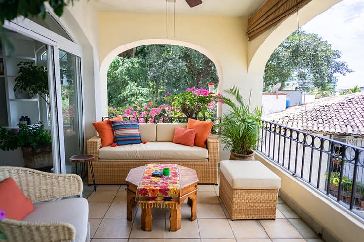 Colorful outdoor seating in a ocean view condo terrace with a balcony.